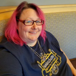 Pictured: White fat woman with pink hair wearing a dark blue 2019 NaNoWriMo shirt